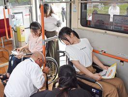 佐賀市交通局職員から車いすの固定方法を教わる学生たち=佐賀市の佐賀女子短期大学