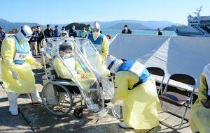 防護服を着た医療関係者らに、ビニールで覆った車いすに乗せられる患者役の男性(中央)=唐津市東大島町の唐津東港