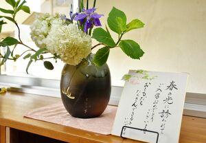 新入生へのお祝いメッセージと一緒に校舎に飾られている生け花