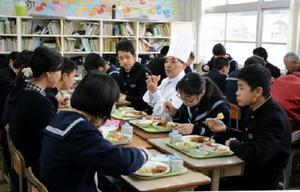 川原純一さん(中央)や教員と机を囲み特別メニューの給食を楽しむ西有田中3年生=有田町の同校