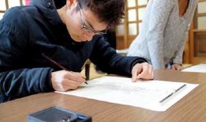 仏の絵を薄い紙に透けさせ、なぞって描き写す「写仏」を体験する参加者=基山町