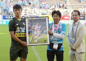月間MVPの趙東建選手(左)とプレゼンターの杉谷龍二さん。右は佐賀新聞社の藤戸隆執行役員技術センター長=鳥栖市のベストアメニティスタジアム