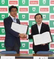 協定を結び、握手するコカ・コーラウエストの本坊俊一郎九州営業本部長(右)と小松政市長=武雄市役所
