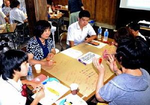 テーブルの紙にメモを書き留めながら意見を交わす参加者たち=嬉野市塩田町の杉光陶器店「三の蔵」