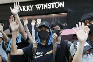 「覆面禁止法」の施行などに抗議し、マスク姿でデモに参加する人たち=10月、香港(共同)