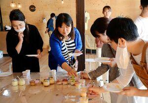 プリンを試食して弾力や食味を評価するメンバー=佐賀市唐人のライトハウス