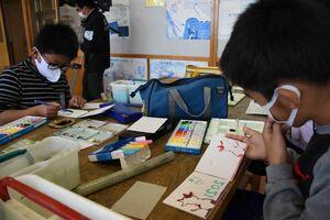 絵の具を板にのせ、版画で年賀状を作る子どもたち=唐津市の湊小学校