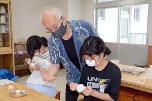 松尾嘉之さんの指導で風鈴に絵付けをする児童ら=有田町の有田小