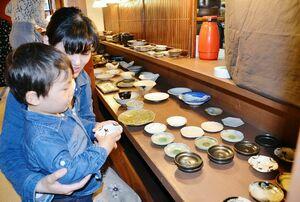 前回の唐津やきもん祭りで、好みの器を選ぶ親子連れ=2019年、唐津市中町の「hanaはな家」