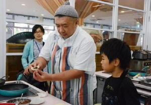 有明海産の具材を使ったギョーザの作り方を指導するパラダイス山元さん=佐賀市の県国際交流プラザ