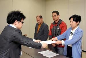 知事の同意を撤回し、玄海原発を再稼働しないよう求める要請書を手渡す吉田恵子世話人(右)=佐賀県庁