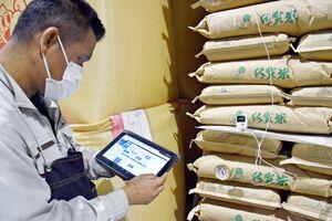 タブレットを手に倉庫内を巡回する担当者。コードが見えるのは穀物の温度を測るセンサー、下は従来のアナログ温度計=佐賀市嘉瀬町、JAさが流通センター