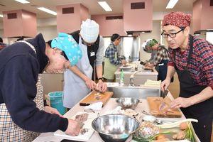 藤吉和男さん(右)から手ほどきを受けて魚を調理する参加者=佐賀市のアバンセ