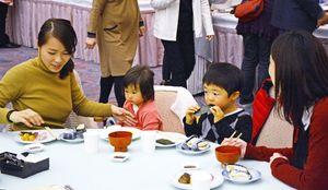 試食会で初摘みのノリを使った料理を味わう家族連れ=佐賀市のガーデンテラス佐賀(マリトピア)