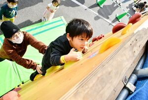 ボルダリングに懸命に挑戦する子どもたち=佐賀市の佐賀商工ビル駐車場
