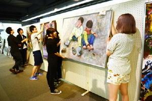 佐賀美術協会の第100回記念展に向け、作品の飾り付けが進む会場=佐賀市の県立美術館・博物館