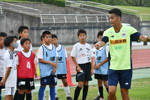 子どもたちに熱く指導するサガン鳥栖の片渕浩一郎ヘッドコーチ(右)=鹿島市陸上競技場
