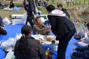 花見客にあいさつをして回る佐賀県議選の候補者=鳥栖市内(一部を画像加工しています)