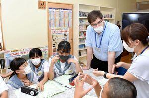 英語での討論内容をALTと考える生徒たち=唐津市肥前町の肥前中学校