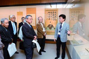 展示資料を解説する佐賀城本丸歴史館の藤井祐介学芸員(右)=佐賀市の同館