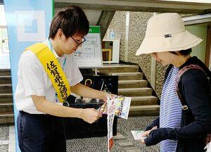 反射材やチラシを配布する県職員=佐賀市の県立図書館(佐賀県提供)