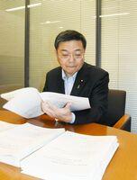 新型コロナウイルスに伴う政府の支援策をまとめた冊子を作成し、内容を確認する古川氏=東京・永田町の事務所