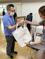 受け付けを済ませ、ユニホームの入ったバッグを受け取って更衣室へ=10日午後6時ごろ、佐賀市役所