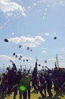海風を感じながら制帽を宙に投げ、旅立ちを喜び合う卒業生=唐津市東大島町