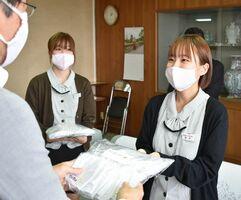 深浦弘信市長(左)に自社製のマスクを手渡す「伊万里セロリー」の社員=伊万里市役所