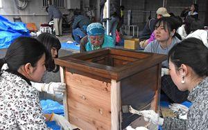 フラワーポットの木箱にはけで塗装をする参加者たち=佐賀市呉服元町の旧佐賀銀行呉服町支店周辺