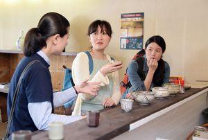 陶芸作家(左)に焼き物の説明を受けながら地酒を飲む来場者。角打ちバーでは、毎晩日替わりで作家が店主を務める=昨年の唐津やきもん祭り