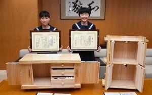 「全国中学生創造ものづくり教育フェア」の作品コンクールで入賞した山内中3年の坂口みきさん(左)、丸田佳乃羽さんと、それぞれの作品