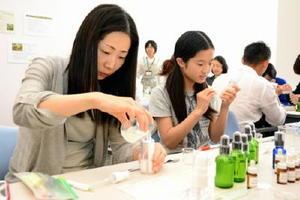 吟味したアロマオイルを蒸留水と混ぜ合わせる参加者=唐津市南城内の大手口センタービル