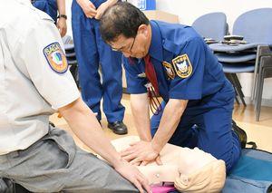救急救命士(左)の指導を受け、胸骨圧迫の訓練をする中央警備保障の社員=佐賀市の同社