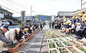 プランターに花を植える脊振小の児童や地元の老人クラブのメンバーたち=神埼市脊振町