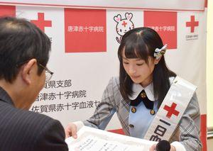 松山所長から委任状を受け取る川原さん=佐賀市の献血プラザ佐賀