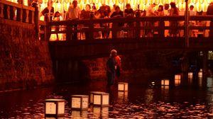 大勢の人たちに見守られながら、多布施川を流れる灯籠=15日午後8時ごろ、佐賀市の護国神社