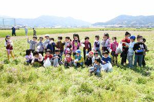 レンゲソウをたくさん摘み取り、笑顔を見せた子どもたち=唐津市山本