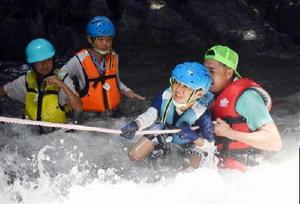 大人の力を借りながら、ロープを頼りに川を上る参加者の子どもたち=唐津市七山の滝川川