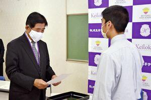 岩永和真生徒会長(右)に文書を手渡す谷口太一郎理事長=伊万里市の敬徳高