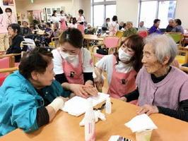 施設利用者らにハンドマッサージを施すエステティシャンたち=佐賀市巨勢町の有料老人ホーム「花みずき」