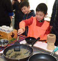 フライパンでフェアトレードのコーヒー豆をいる参加者ら=佐賀市の国際交流プラザ