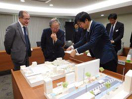 模型を使って駅前広場の整備計画を確認する荒牧座長(中央)=佐賀市役所