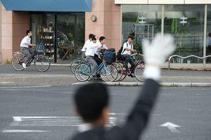通学中の高校生らに手を振る立候補予定者=28日午前8時ごろ、佐賀市与賀町交差点