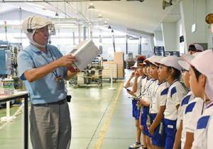 藤瀬光利工場長から製造過程の説明を聞く子どもたち=佐賀市のサガシキ九州佐賀工場