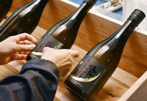 完成した光栄菊酒造の新酒。ラベルが貼られ、次々に箱詰めされていく=小城市三日月町