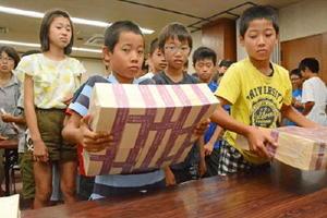 重さ約10㌔の模造紙を持ち上げる子どもたち=佐賀市の佐賀共栄銀行本店