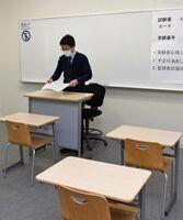 試験室の設営をする担当者=佐賀市神園の西九州大学佐賀キャンパス