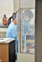 新型コロナウイルスの検査に当たり、試薬の調整をする担当職員ら=佐賀市八丁畷町の県衛生薬業センター
