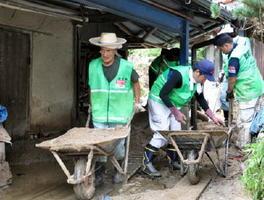 家屋周囲の土砂を運び出す「チーム武雄」のボランティア=福岡県朝倉市杷木の白木地区